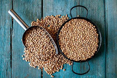 Skillet and metal scoop with dried brown lentils on wood - p300m1130112f von Kiko Jimenez