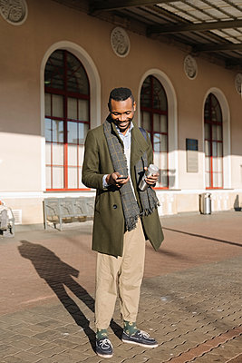 Stylish man with reusable cup using smartphone while waiting for the train - p300m2154582 by Hernandez and Sorokina