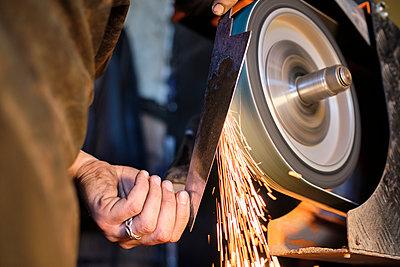 Male blacksmith sharpening knife shape metal on grinder at workshop - p300m2281462 by Antonio Ovejero Diaz