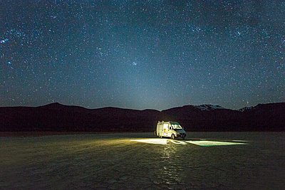 ALVORD DESERT, HARNEY COUNTY, OR, USA. A white van is parked in a giant dried lake bed at night under a starry, Milky Way sky with what appears to be a halo of light around the van. - p343m1167980 by David Hanson