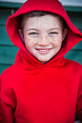 Portrait of happy boy with face freckles wearing red hoody - p429m1084508 by Christopher Villano