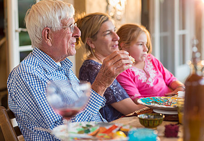 Caucasian family eating at table outdoors - p555m1411392 by Marc Romanelli