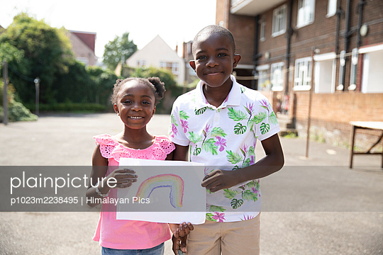 Portrait cute brother and sister holding rainbow drawing outside - p1023m2238495 by Himalayan Pics