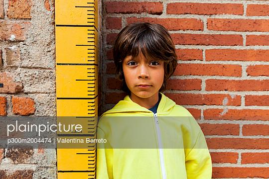 Portrait of sceptical boy leaning against yardstick - p300m2004474 von Valentina Barreto