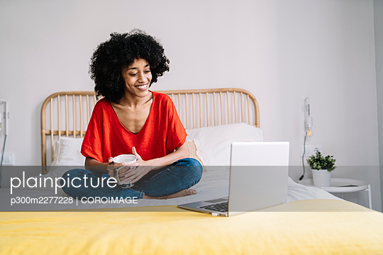 Young woman with mug looking at laptop while sitting on bed at home - p300m2277228 by COROIMAGE