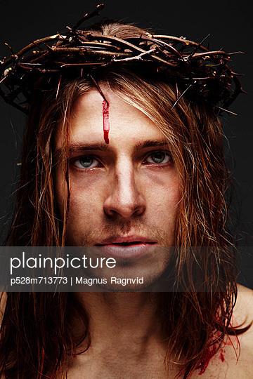 Young man as Jesus wearing crown of thorns, studio shot