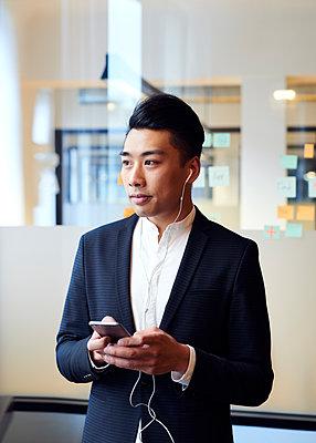 Asiatischer Mann telefoniert mit Headset - p1124m1181491 von Willing-Holtz