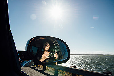 Woman photographing while reflecting on side-view mirror of car against sky - p1166m1524537 by Cavan Images