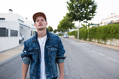 Portrait of young man in denim jacket standing on the street - p300m2083034 by Andrés Benitez