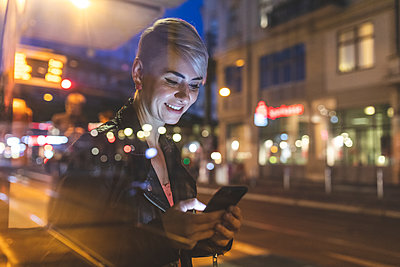 Portrait of smiling blond woman at tram stop looking at mobile phone, Berlin, Germany - p300m2144979 by William Perugini