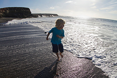 Boy playing in waves on beach - p42918348f by jackSTAR