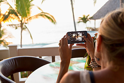 Caucasian woman photographing sunset at beach - p555m1305325 by Marc Romanelli