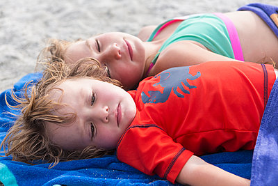 Caucasian brother and sister napping on beach - p555m1411370 by Marc Romanelli