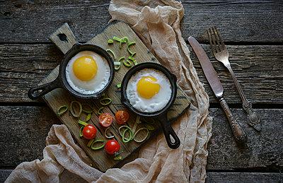 Fried eggs in cast iron pans on cutting board - p555m1472988 by Valeriya Tikhonova
