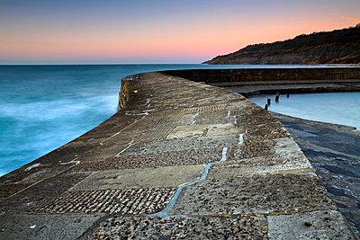 Dawn on the stone walls of The Cobb - p8714081 by Adam Burton