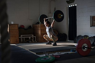 Crossfitter lifting barbell in gym - p924m1067222f by Kinzie Riehm
