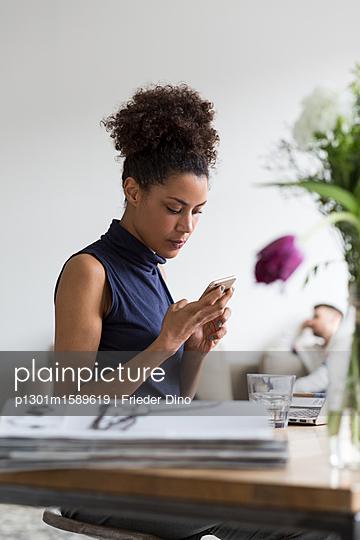 Junge Geschäftsfrau sitzt am Arbeitsplatz und sieht auf ihr Handy  - p1301m1589619 von Delia Baum