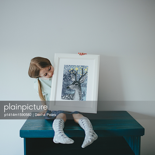 Girl holding a picture - p1414m1590582 by Dasha Pears