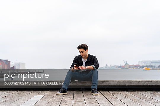 Denmark, Copenhagen, young man sitting at the waterfront using cell phone - p300m2102149 by VITTA GALLERY