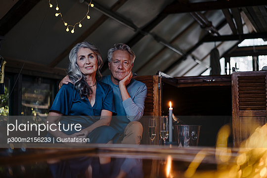 Portrait of senior couple having a candlelight dinner on a boat in boathouse - p300m2156233 by Gustafsson