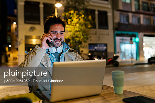 Man with laptop talking on mobile phone while sitting at sidewalk cafe - p300m2251082 by Ezequiel Giménez