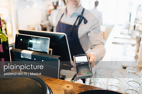Midsection of man holding credit card reader in restaurant - p426m2149170 by Maskot