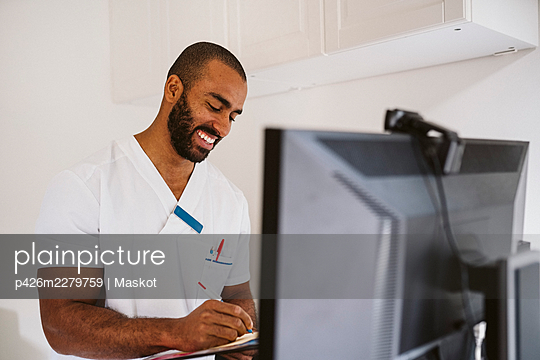 Smiling male healthcare worker writing while consulting patient through video call - p426m2279759 by Maskot