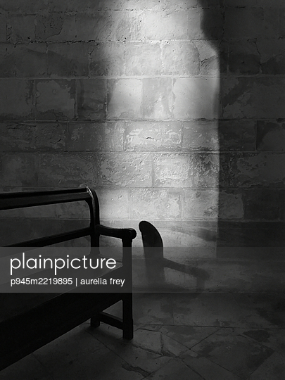 Black bench against stone wall - p945m2219895 by aurelia frey