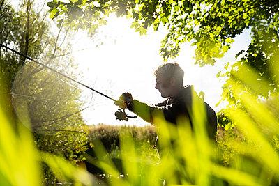 Man preparing fly fishing line under sunny tree - p1023m2262069 by Martin Barraud