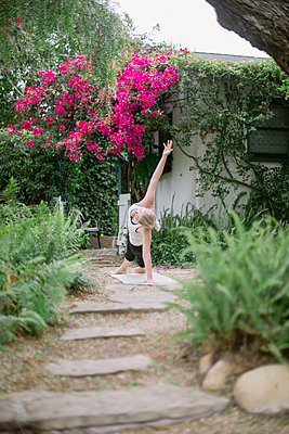 Blond woman doing yoga in a garden. - p1100m1080230 by Mint Images