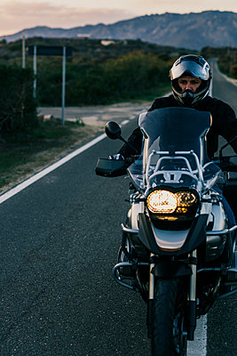 Lonely biker riding on an empty road - p1165m1541060 by Pierro Luca