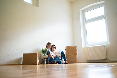 Mature couple sitting on floor in empty room next to cardboard boxes using tablet - p300m1562194 by Robijn Page