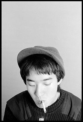 Man in hat lighting cigarette - p3720272 by James Godman