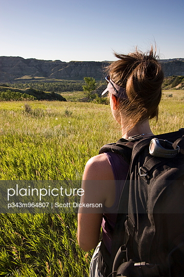 An adult woman backpacks in a national park in North Dakota. - p343m964807 by Scott Dickerson