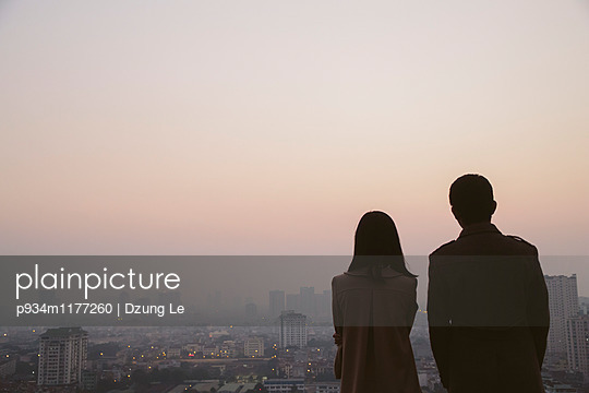 A young vietnamese couple contemplate a skyline cityscape at dusk in Hanoi, Vietnam, Southeast Asia - p934m1177260 by Dzung Le photography