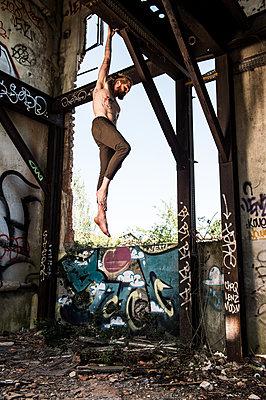 Man hangs on to wooden beam - p1139m2027764 by Julien Benhamou