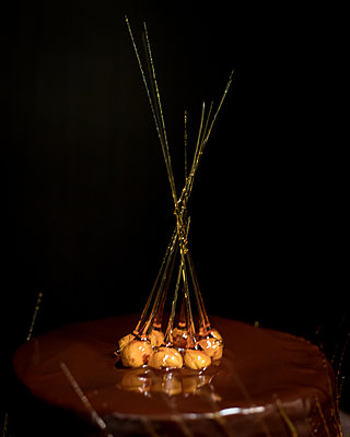 Candied Hazelnut Skewers Atop a Chocolate Mirror Glazed Cake - p1166m2169220 by Cavan Images