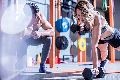 Fitness instructor with woman doing dumbbell press ups in gym - p300m1204576 by zerocreatives