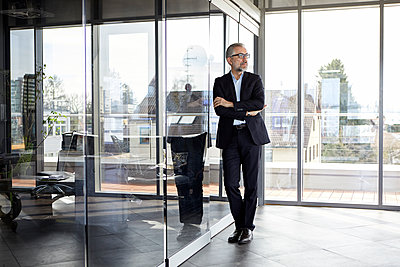 Businessman standing in office thinking - p300m2012956 von Rainer Berg