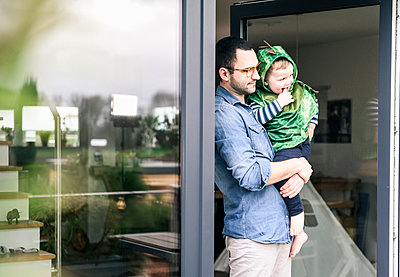 Father carrying son in a costume at terrace door at home - p300m2104430 by Uwe Umstätter