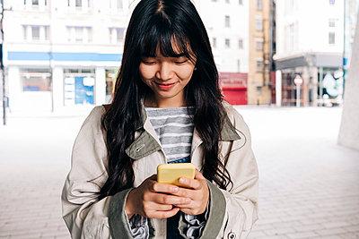 Smiling woman text messaging through smart phone in city - p300m2298983 von Angel Santana Garcia