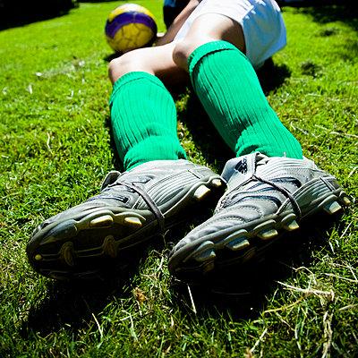 Football player lying on lawn - p4264867f by Tuomas Marttila
