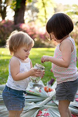 Girl and toddler sister with green anole lizard and jar in garden - p924m937078f by Kinzie Riehm