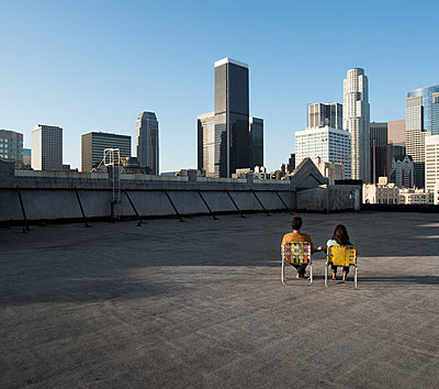 A couple, man and woman sitting in deck chairs on a rooftop overlooking city skyscrapers.  - p1100m1107170 by Mint Images