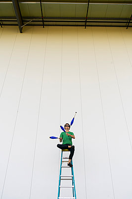 Acrobat wearing sunglasses, sitting on ladder, juggling - p300m2012358 by VITTA GALLERY