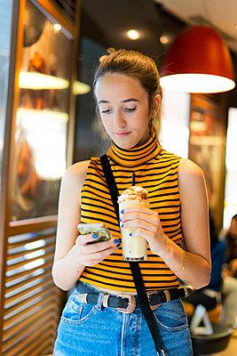 Spain, teenage girl with milk shake using smartphone - p300m2103158 by Eloisa Ramos