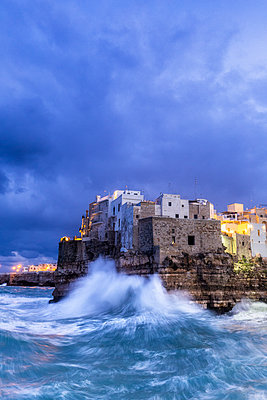 Waves crash on the cliff during a winter storm at dusk, Polignano a Mare, Apulia, Italy, Europe - p871m2209746 by Francesco Bergamaschi