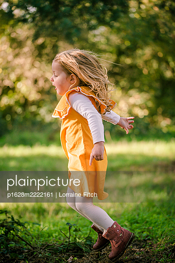 Toddler in a yellow dress with blonde hair running in a sunny woodland - p1628m2222161 by Lorraine Fitch