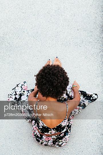 Weiblicher Teenager mit Sommerkleid auf Betonboden - p728m2038855 von Peter Nitsch
