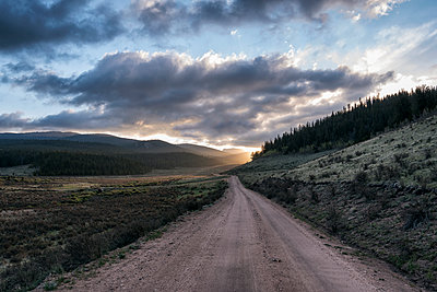 Empty dirt road amidst landscape against cloudy sky during sunset - p1166m1571104 by Cavan Social